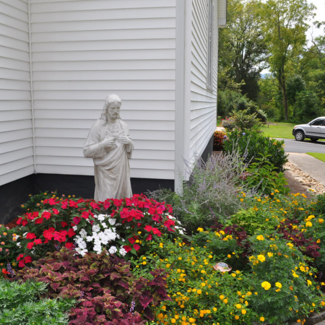Sacred Heart Statue with Flowers